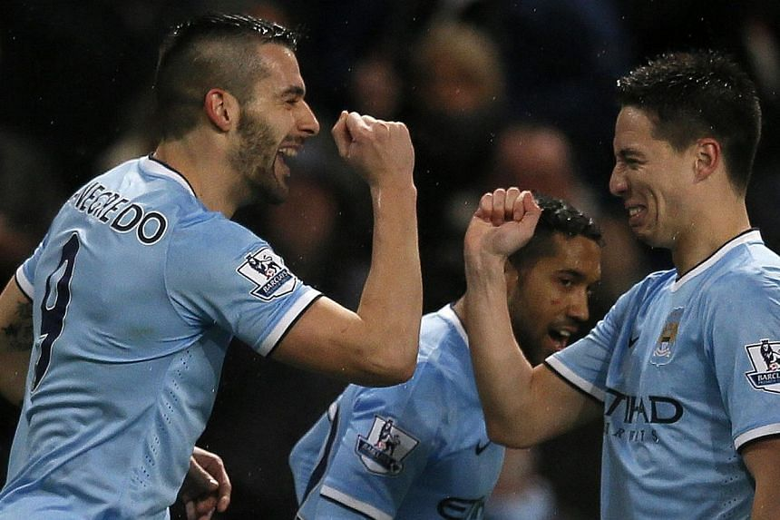 Manchester City's Alvaro Negredo (left) celebrates scoring with Samir Nasri against West Ham United during their English League Cup semi-final first leg soccer match at the Etihad Stadium in Manchester, northern England Jan 8, 2014.Negredo grab
