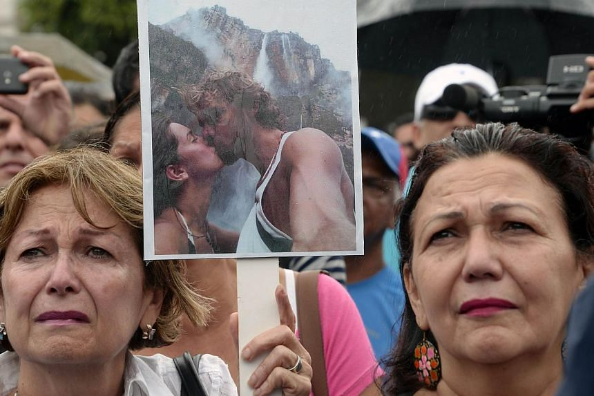 People mourning the death of former beauty queen Monica Spear at a protest in Caracas on Jan 8, 2014. Gunmen killed Ms Spear and her partner Thomas Henry Berry in front of their young daughter in an attack that shocked the crime-plagued nation. PHOTO