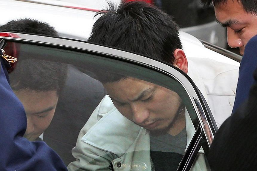 Yuta Sugimoto (centre), who slipped away from his guard during a visit to prosecutors in an office building on Jan 7, arrives at the prosecutors office in Kawasaki, suburban Tokyo on Jan 9, 2014, after he was arrested in Yokohama, near Kawasaki. -- P