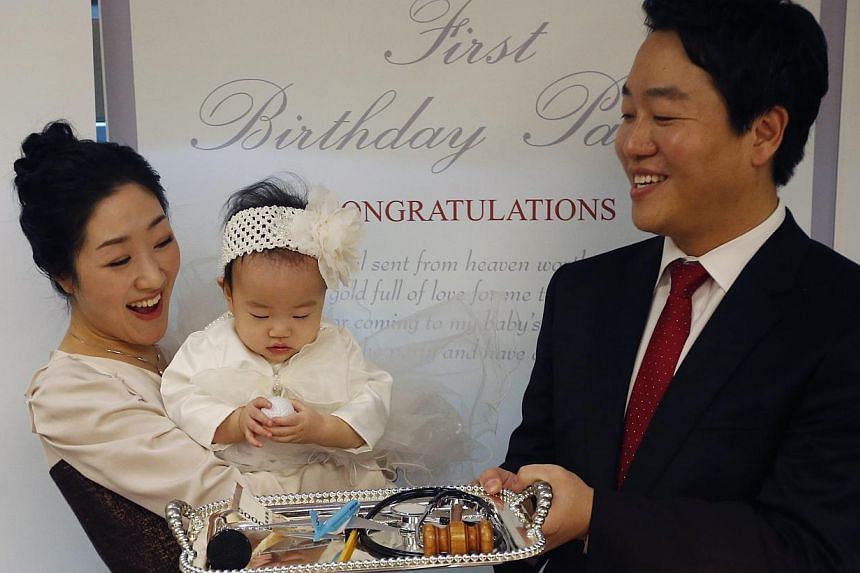 Kim Dot Byul picks up a golf ball among various items for Doljabi on a tray during her first birthday party, or Doljanchi in Korean, in Seoul on Dec 14, 2013. It takes a lot more than a cake and a song to celebrate a baby's first birthday in South Ko