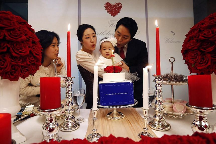 Kim Dot Byul and her parents blow a candle during her first birthday party, or Doljanchi in Korean, in Seoul on Dec 14, 2013. -- FILE PHOTO: REUTERS