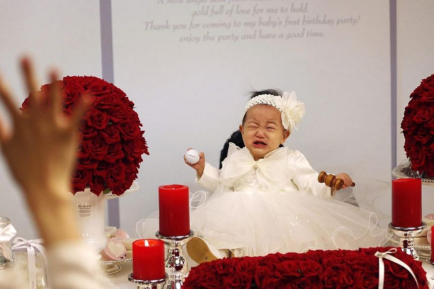 Kim Dot Byul cries as she poses for photographs with a golf ball during her first birthday party, or Doljanchi in Korean, in Seoul on Dec 14, 2013. -- FILE PHOTO: REUTERS