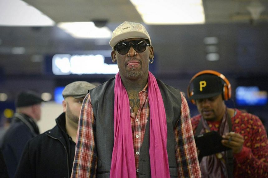 Former NBA basketball player Dennis Rodman of the United States (centre) waits to check in for his flight to North Korea after his arrival at Beijing's international airport on Jan 6, 2014. -- FILE PHOTO: AFP