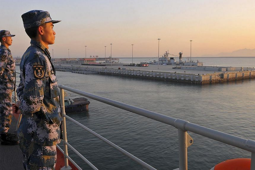 Chinese naval soldiers stand guard on China's first aircraft carrier Liaoning, as it travels towards a military base in Sanya, Hainan province. -- PHOTO: REUTERS