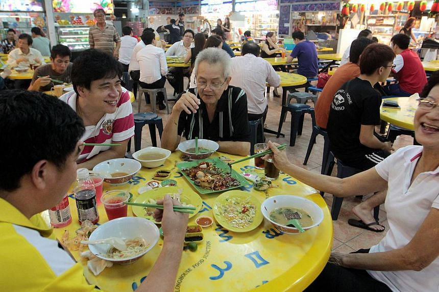 (From right) Madam Goh Siew Choo, 69, Mr Yap Sowi Tee, 71, Mr Raymond Yap, 42, and Mr K.T. Yap, 46, enjoying a late dinner at Long House. Patrons say that they will miss the food when the stalls move out.-- ST PHOTOS: NEO XIAOBIN