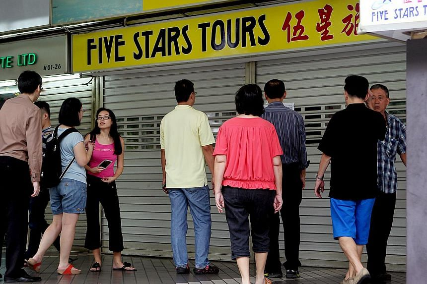 People milling about outside the Five Stars Tours branch at Golden Mile Complex yesterday. -- ST PHOTOS: LAU FOOK KONG