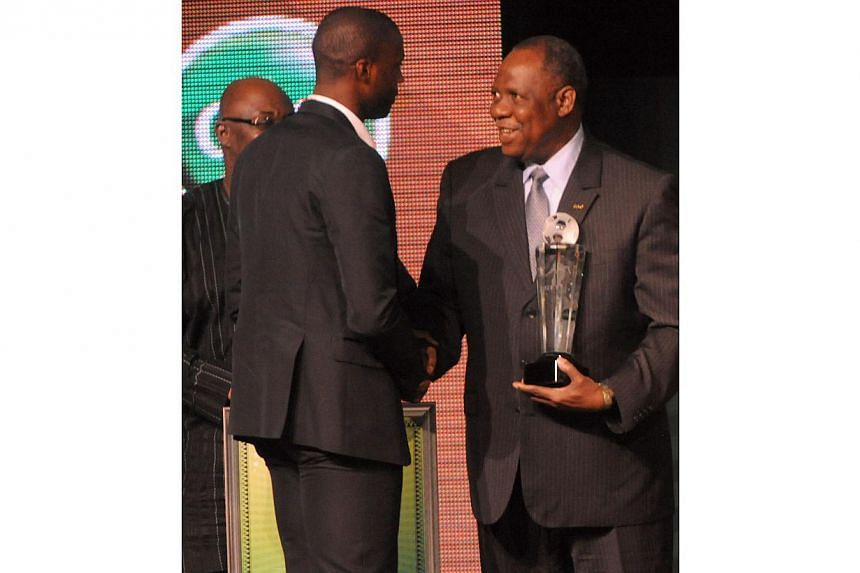 CAF President Issa Hayatou (right) shakes hands and tries to present the trophy to Manchester City midfielder Yaya Toure after winning the CAF African Footballer of the Year Award in Lagos on Jan 9, 2014. -- PHOTO: AFP