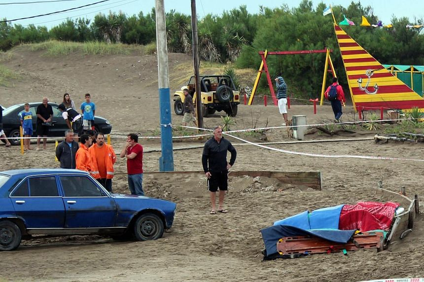 People remain near a corpse after a lightning killed three tourists in Villa Gesell, Argentina, on Jan 9, 2014. The incident injured 15 others. -- PHOTO: AFP