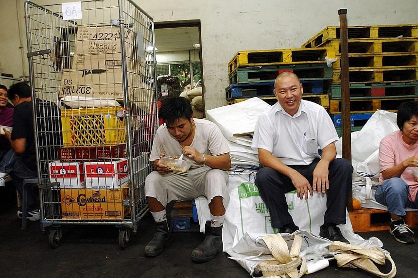 Mr Lim Hock Chee, then the managing director of Sheng Siong, sitting with his workers during lunch in a photo from 2004. -- ST FILE PHOTO: HOW HWEE YOUNG