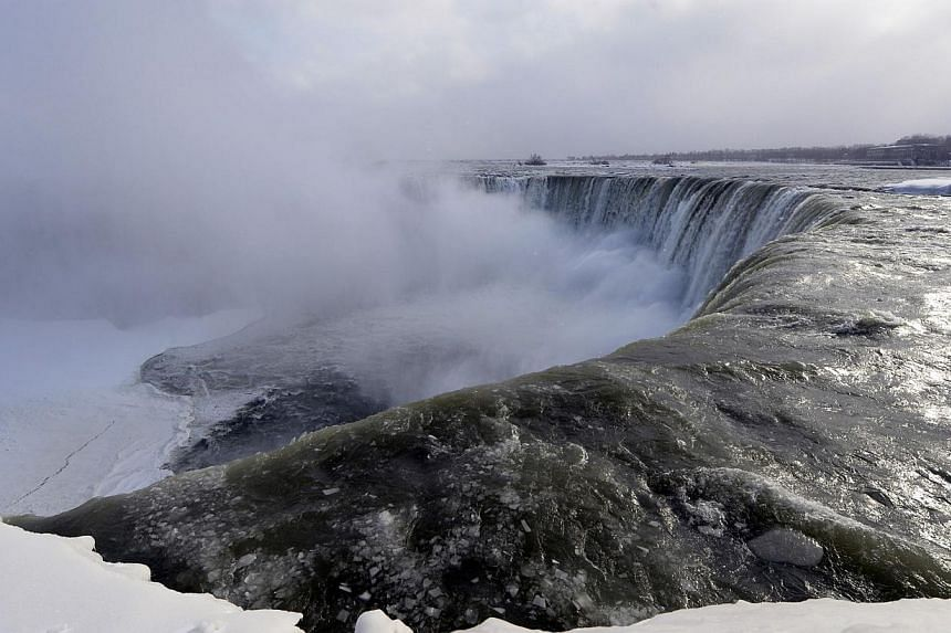 Ice chunks and water flow over the falls Niagara Falls, Ontario, on Jan 8, 2014. -- PHOTO: REUTERS