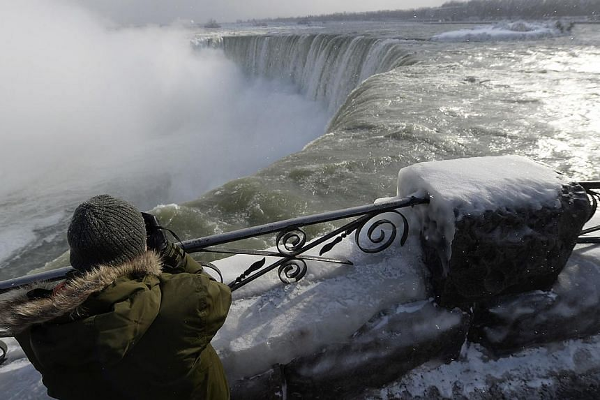 A visitor takes pictures overlooking the falls in Niagara Falls, Ontario, on Jan 8, 2014. -- PHOTO: REUTERS