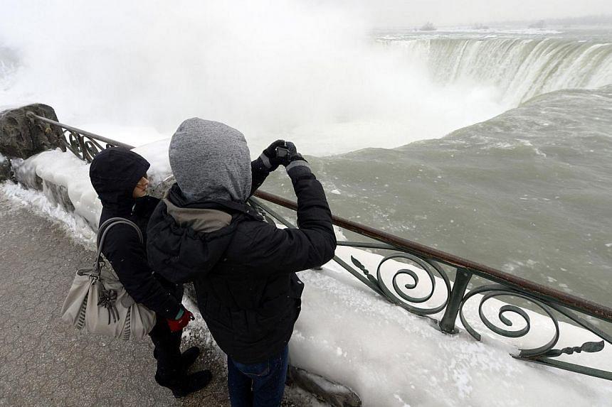 Visitors take pictures overlooking the falls in Niagara Falls, Ontario, on Jan 8, 2014. -- PHOTO: REUTERS