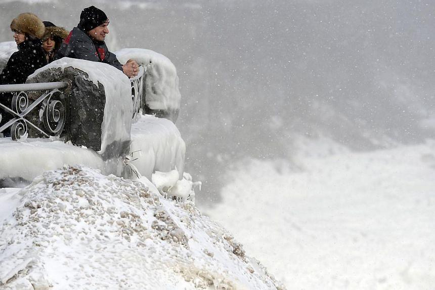 Visitors observe the falls in Niagara Falls, Ontario, on Jan 8, 2014.  -- PHOTO: REUTERS