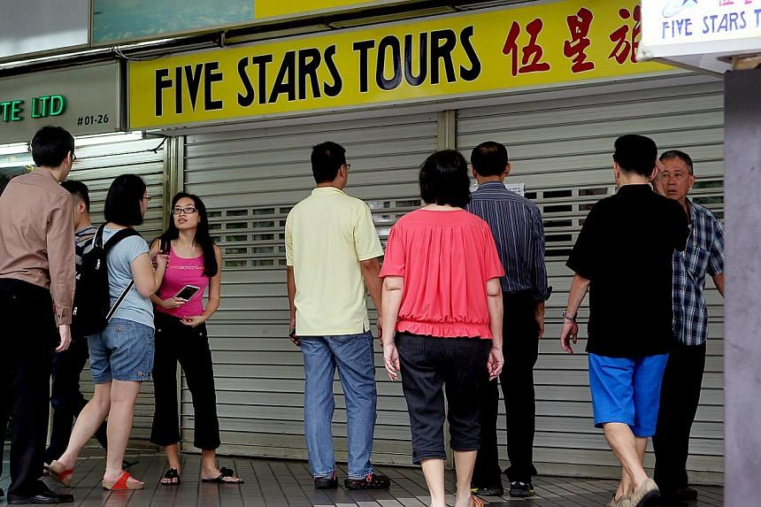 People milling about outside the Five Stars Tours branch at Golden Mile Complex, on Jan 9, 2014. The National Association of Travel Agents (Natas) is working with insurance company AIG Asia Pacific and seven travel agencies to help customers affected
