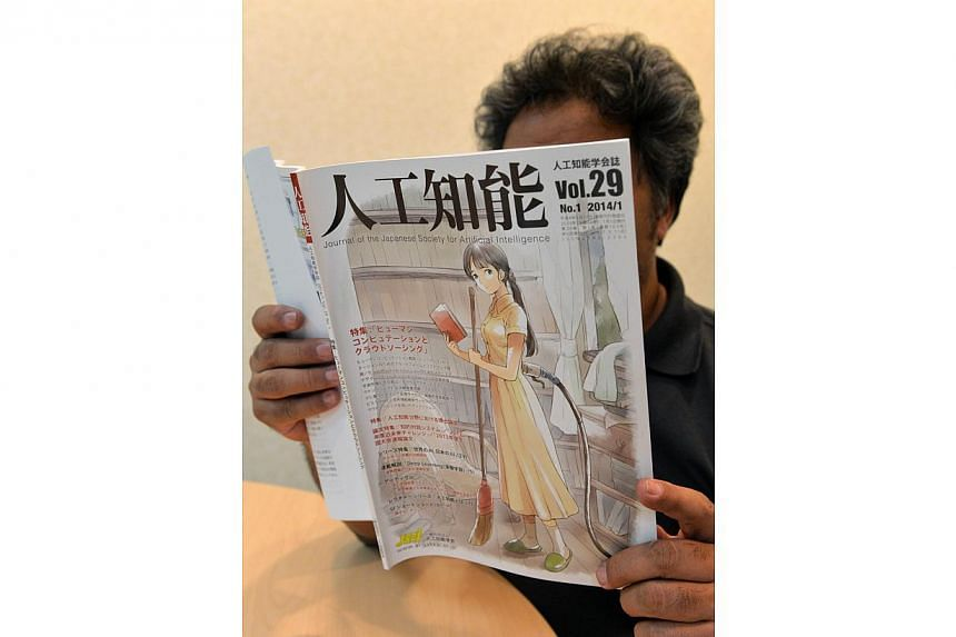 """A man reading the """"Journal of the Japanese Society for Artificial Intelligence Vol.29 No.1"""" in Tokyo, on Jan 10, 2014. A Japanese academic society has apologised for the front cover of their journal, which used a drawing of a cleaning woman with a ca"""