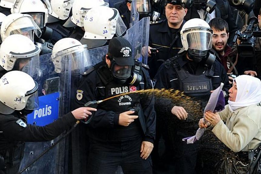 A woman (right) confronts Turkish riot policemen as they spray tear gas on demonstrators trying to march on Jan 9, 2014, in Istanbul, to the French consulate demanding justice for three female Kurdish rebels killed a year ago in Paris. Between 500 to