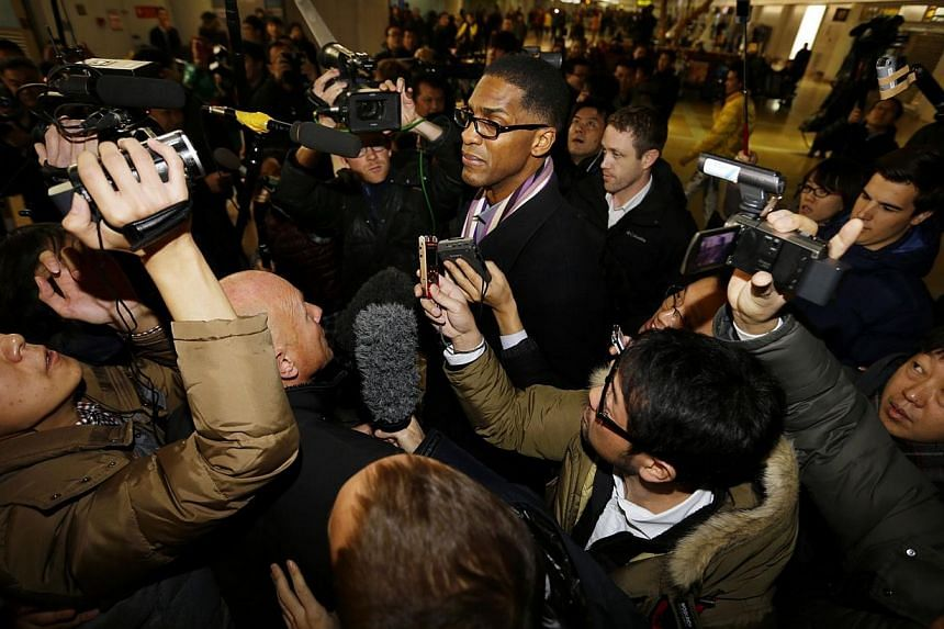Former NBA basketball player Charles Smith is surrounded by the media upon his arrival from North Korea's Pyongyang, at Beijing Capital International Airport, on Jan 10, 2014. Smith said on Friday, Jan 10, 2014, that a basketball game organised by De