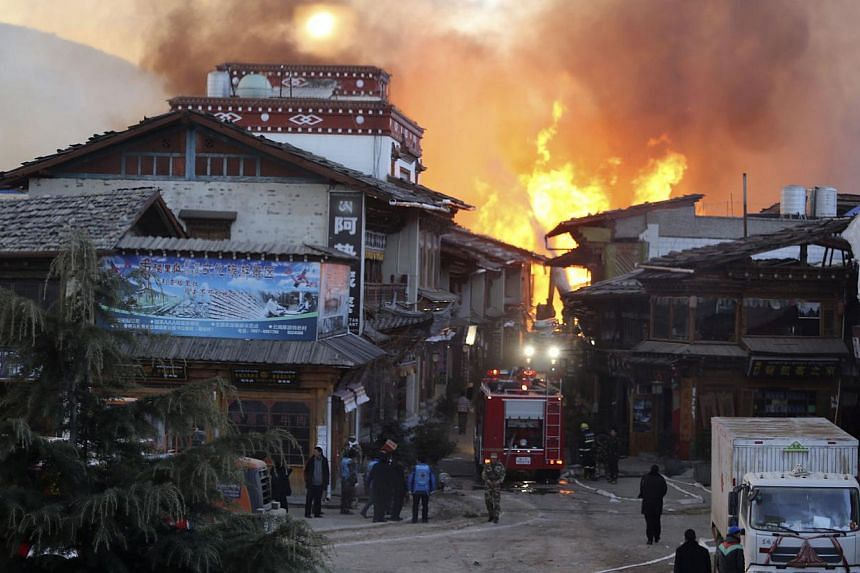 A firefighter truck is seen near a fire at the Dukezong Ancient Town in Shangri-la county, Yunnan province Jan 11, 2014. More than 1,000 people were battling the fire that broke out early Saturday at a resort county in southwest China's Yunnan provin