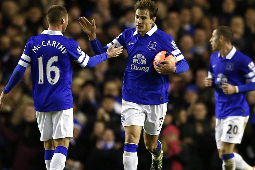 Everton's Nikica Jelavic (centre) celebrates with team mate James McCarthy (left) after scoring a goal against Queens Park Rangers during their English FA Cup soccer match at Goodison Park in Liverpool, northern England, on January 4, 2014.Hull