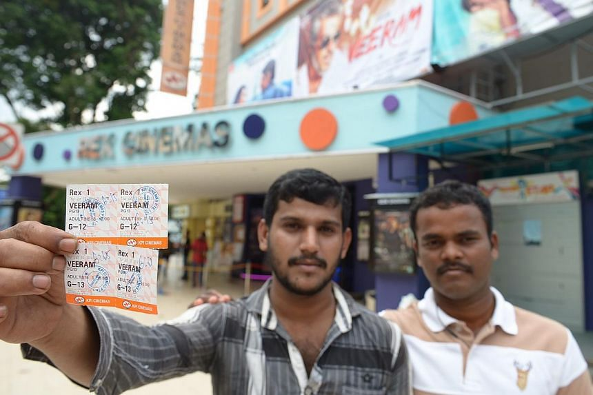 Construction workers Kannan Karthikeyan, 28, and Pichai Rengasamy, 29, showing their tickets for Veeram. After the screening was cancelled, Rex endorsed their tickets for the 6.15pm screening yesterday. -- ST PHOTO: DESMOND WEE