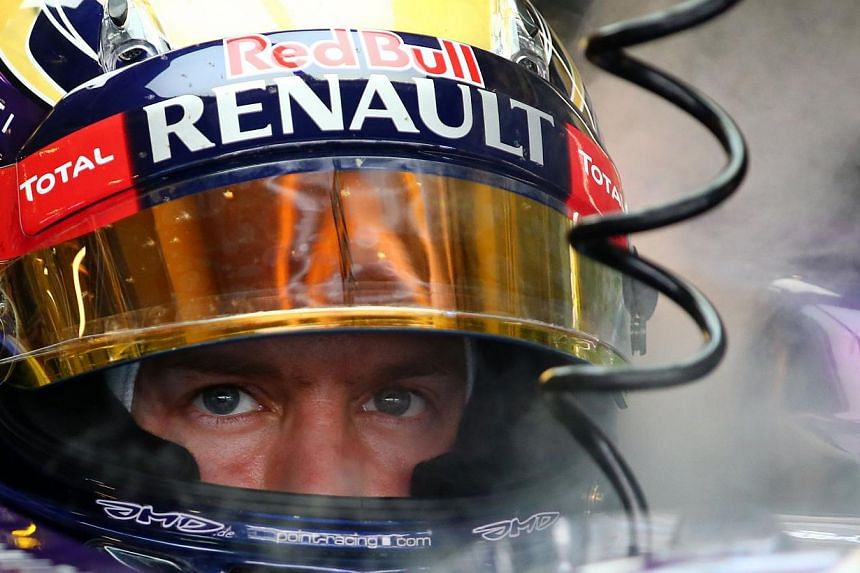 Red Bull Racing's German driver Sebastian Vettel sits in the pits during the third practice session at the Yas Marina circuit in Abu Dhabi on Nov 2, 2013. Quadruple Formula One world champion Sebastian Vettel went for five on Friday with the Ger