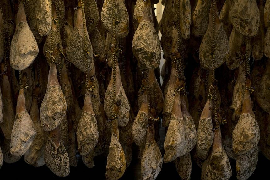 """Hams hang at Ibericos Arturo Sanchez in Guijuelo on May 7, 2013. Spain's government acted on Jan 10, 2014, to protect the global reputation of its prize cured ham, the exquisite ruby-red """"jamon iberico"""", by simplifying labels and tightening quality."""