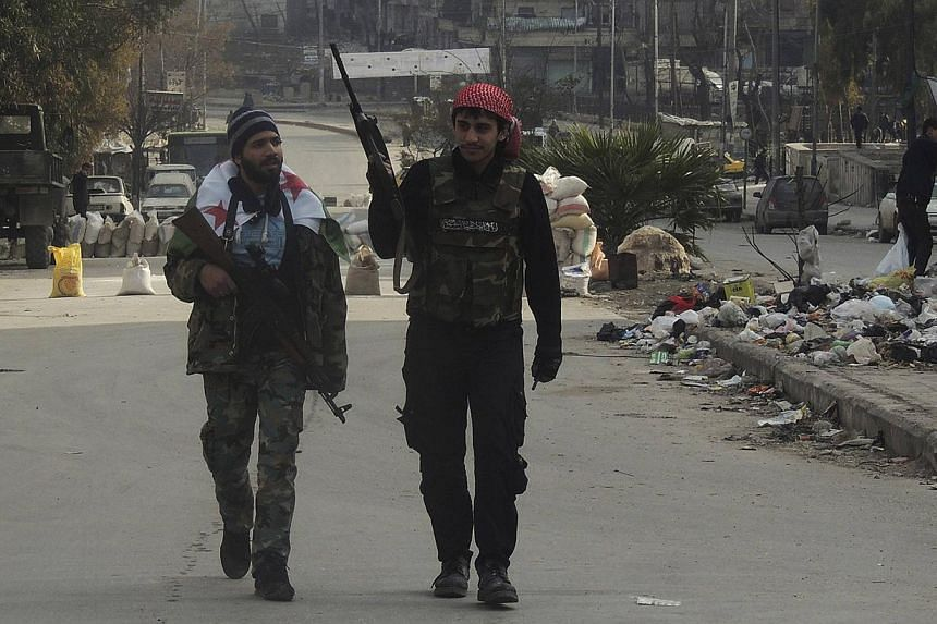 Syrian rebel fighters hold their weapons as they walk along a street in Aleppo's Salaheddine neighbourhood on Jan 10, 2014. Al-Qaeda-linked jihadists struck back against rival rebels in eastern and northern Syria on Friday after a week of inter