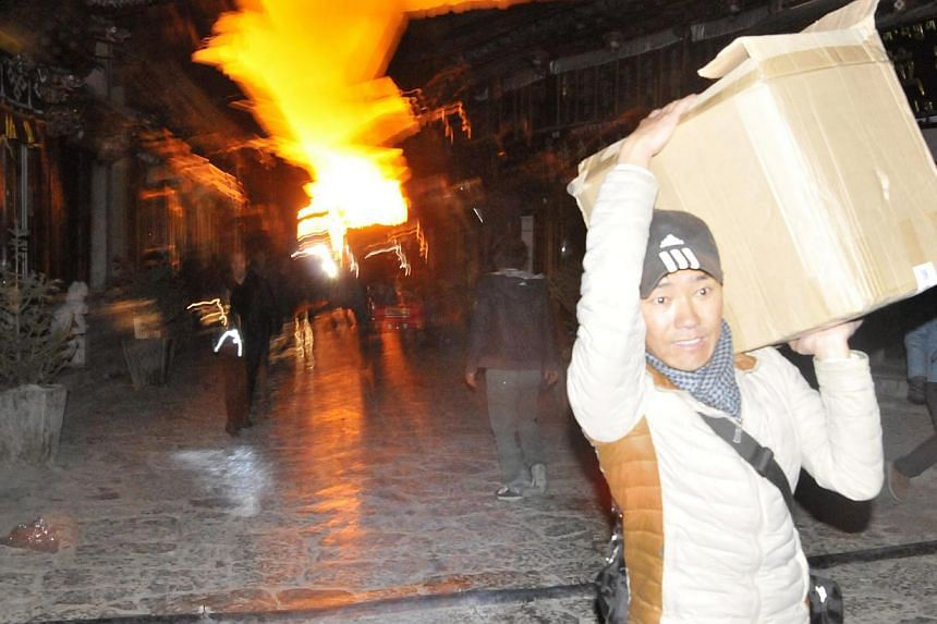 A man carrying his belongings, runs away from a fire at the Dukezong Ancient Town in Shangri-la county, Yunnan province, on Jan 11, 2014. -- PHOTO: REUTERS