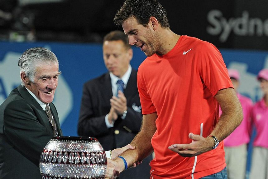 Juan Martin Del Potro of Argentina (right) receives the winners trophy from former Australian tennis player Ken Rosewall (left) following his defeat of Australia's Bernard Tomic in the men's singles final at the APIA Sydney International tennis tourn