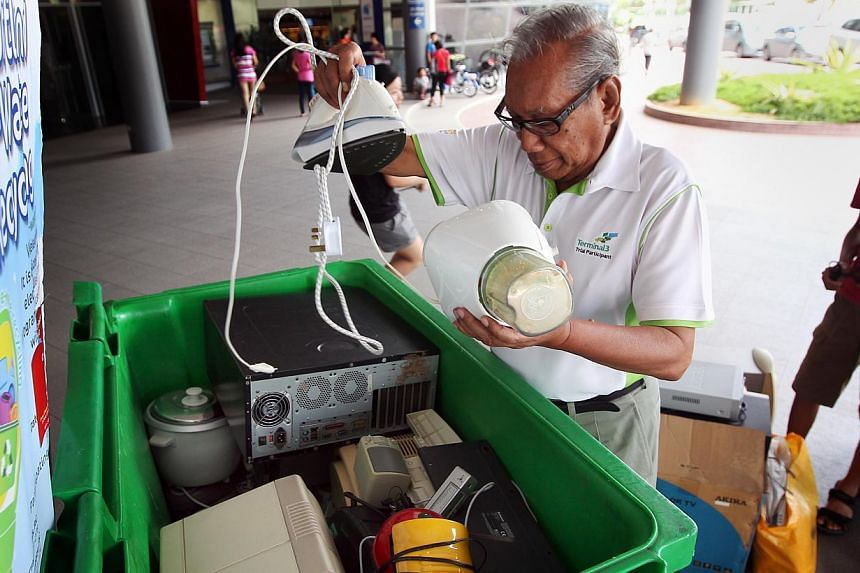 Retiree Hussein Jaafar, 74, puts his used electric applicances in a recycling bin at Marine Parade CC on Saturday, Jan 11, 2014. A trial to collect and recycle disused electronics in one neighbourhood has surpassed initial expectations, with organise