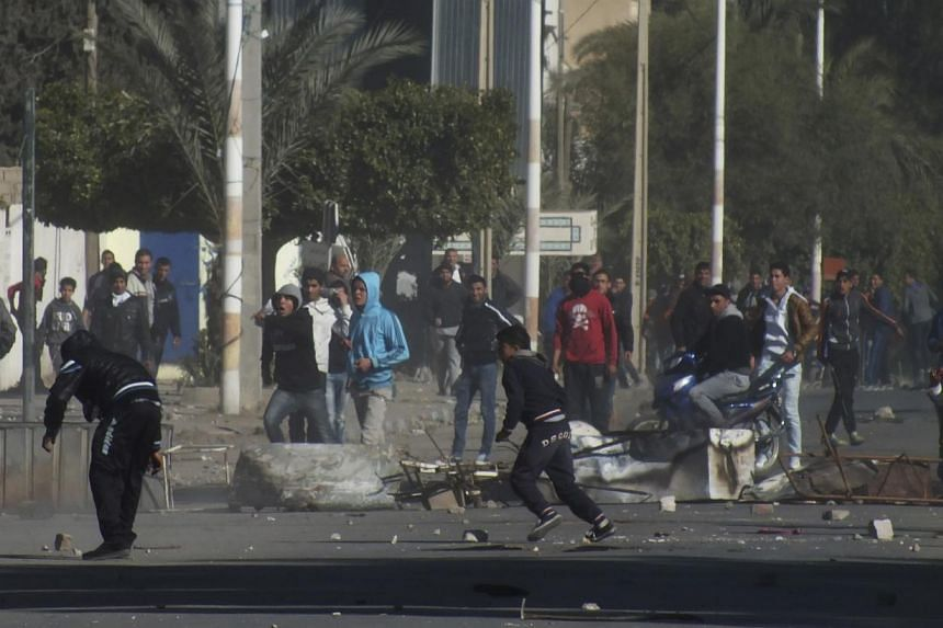 Protesters clash with the police in Kasserine, west Tunisia, on Jan 9, 2014. One man was shot dead in clashes in a Tunisian city near the Algerian border late on Friday after protesters tried to storm a customs office in one of several demonstrations