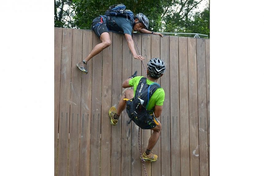 Participants scaling the high wall.-- PHOTO:SAFRA