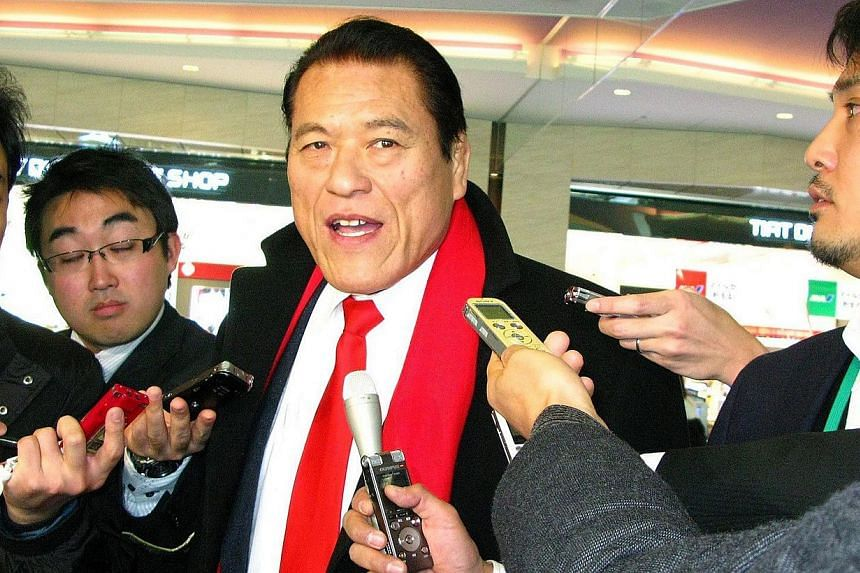 Japanese professional wrestler-turned-lawmaker Antonio Inoki (centre) is surrounded by reporters upon his departure at Haneda Airport in Tokyo on Jan 12, 2013. -- PHOTO: AFP