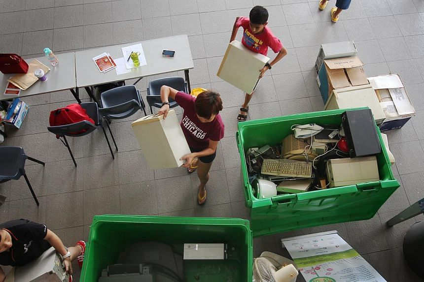 Volunteers, South East CDC staff and Panasonic staff at Marine Parade Community Club packing and sorting items collected yesterday under the e-waste recycling programme. -- ST PHOTO: JASON QUAH