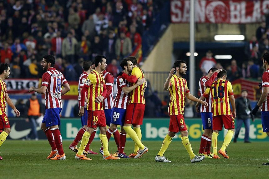 Atletico Madrid and Barcelona's football players react before the Spanish league football match Club Atletico de Madrid v FC Barcelona at the Vicente Calderon stadium in Madrid on Jan 11, 2014. Atletico Madrid and Barcelona remain locked together on