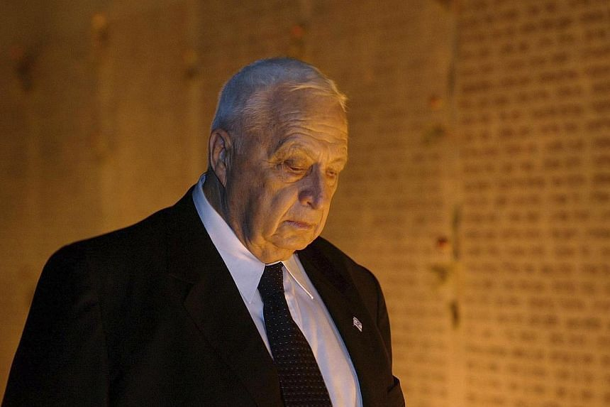 """Israeli Prime Minister Ariel Sharon attends a memorial ceremony at the """"Wall of Names"""" in this Oct 3, 2002 file photo at the Israeli army's Armored Corps' Memorial at Latrun, Israel. Former Israeli premier Ariel Sharon will be buried on Monday aftern"""