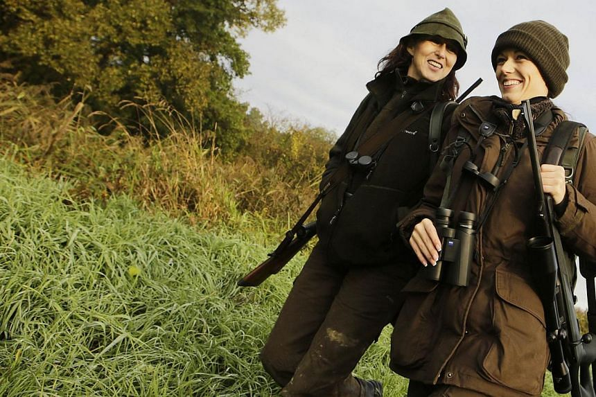 Austrian huntress Petra Schneeweiss (left) and her daughter Elia walk during a stalk at the Szeuizvoelgyi hunting grounds on Oct 12, 2013, near Kisbucsa, Hungary. It's raining hard and almost dark as Walter Rienzner, perched on a raised shooting plat