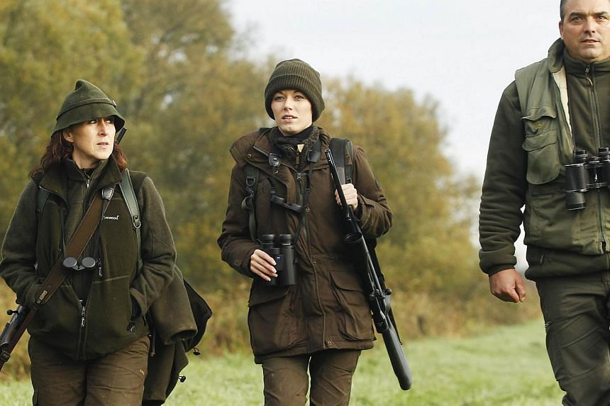 Austrian huntress Petra Schneeweiss (left) and her daughter Elia (centre) walk with Professional Hunter Jozef during a stalk at the Szeuizvoelgyi hunting grounds on Oct 12, 2013, near Kisbucsa, Hungary. -- FILE PHOTO: AFP