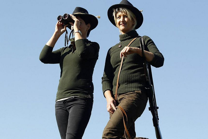 Austrian huntress Evelin Grubelnig (right) and her sister Ingrid Kuchling are pictured during a morning stalk at the Szeuizvoelgyi hunting grounds on Oct 12, 2013, near Kisbucsa, Hungary. -- FILE PHOTO: AFP