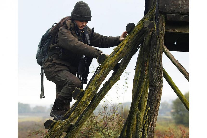 Austrian huntress Elia Schneeweiss climbs on a highstand during a morning stalk at the Szeuizvoelgyi hunting grounds on Oct 12, 2013, near Kisbucsa, Hungary. -- FILE PHOTO: AFP