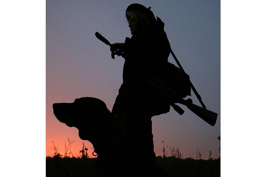 Austrian huntress Evelin Grubelnig is pictured with her Hanoverian Bloodhound during a morning stalk at the Szeuizvoelgyi hunting grounds on Oct 12, 2013, near Kisbucsa, Hungary. -- FILE PHOTO: AFP