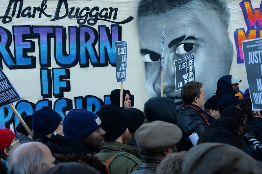 People stand beside a banner depicting Mark Duggan, who was shot dead by police, outside Tottenham Police Station in London on Jan 11, 2014, during a vigil following a jury verdict on Jan 8, 2014 ruling that Mark Duggan was lawfully killed when he wa