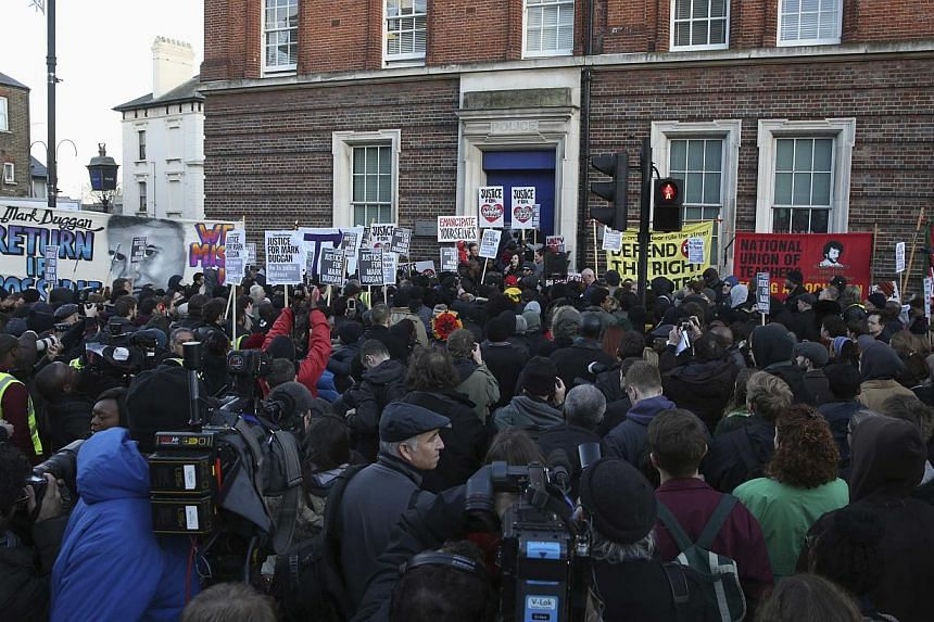 Crowds gather at a vigil for Mark Duggan, outside Tottenham Police Station in Tottenham, north London on Jan 11, 2014. -- PHOTO: REUTERS