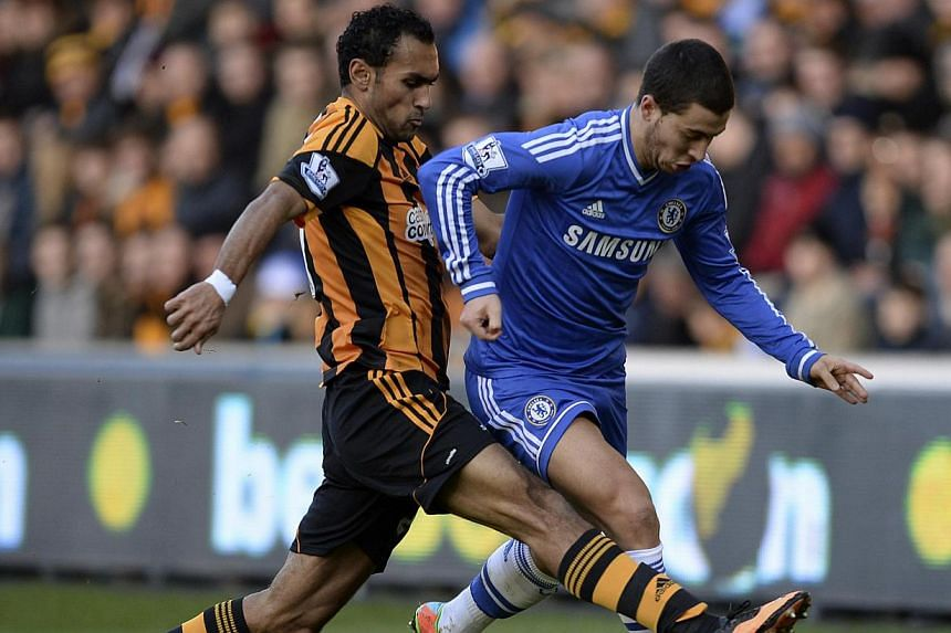 Hull City's Ahmed Elmohamady (left) challenges Chelsea's Eden Hazard during their English Premier League soccer match at The KC Stadium in Hull, northern England on Jan 11, 2014. -- PHOTO: REUTERS