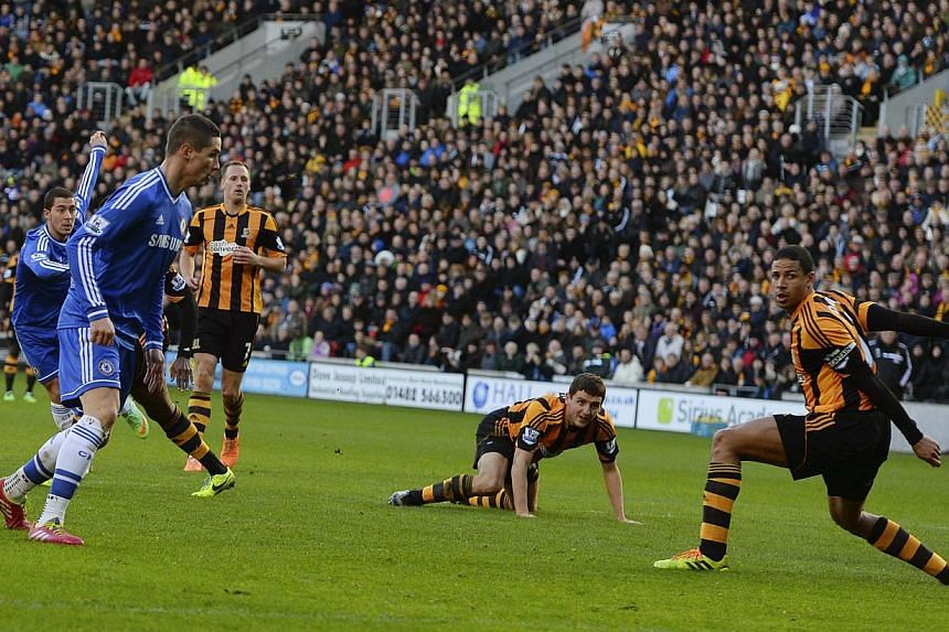 Chelsea's Eden Hazard (left) shoots and scores his goal against Hull City during their English Premier League soccer match at The KC Stadium in Hull, northern England on Jan 11, 2014. -- PHOTO: REUTERS