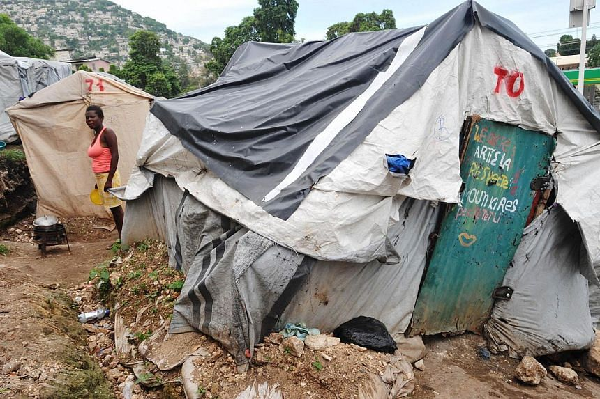 A young woman prepares food on Nov 1, 2013, at camp Acra in Pétion-ville, Haiti, where victims of the Jan 2010 eartquake are living in makeshift tents. Four years after Haiti was hit by a violent earthquake, the dragging pace of reconstruction is no