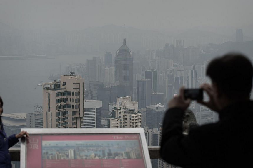 This picture taken on Jan 9, 2014, shows tourists taking a souvenir picture as a haze of toxic pollution is seen over Hong Kong. -- PHOTO: AFP