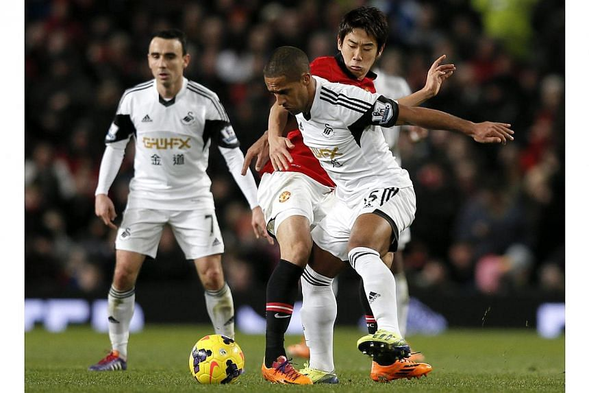 Manchester United's Shinji Kagawa challenges Swansea City's Wayne Routledge during their English Premier League soccer match at Old Trafford in Manchester, northern England on Jan 11, 2014. -- PHOTO: REUTERS