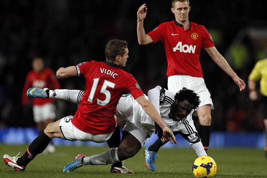 Manchester United's Nemanja Vidic (left) and Darren Fletcher (right) challenge Swansea City's Wilfried Bony during their English Premier League soccer match at Old Trafford in Manchester, northern England on Jan 11, 2014. -- PHOTO: REUTERS