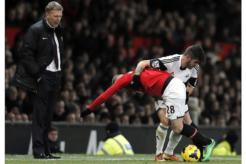 Manchester United's Alexander Buttner (centre) challenges Swansea City's Alejandro Pozuelo as his manager David Moyes (left) watches during their English Premier League soccer match at Old Trafford in Manchester, northern England on Jan 11, 2014. --